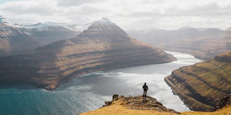 Faeroer-eilanden-persoon-kijkt-uit-over-bergen-en-zee