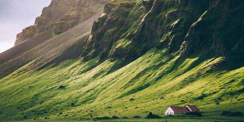 IJsland-in-de-zomer-huisje-tegen-groene-berg