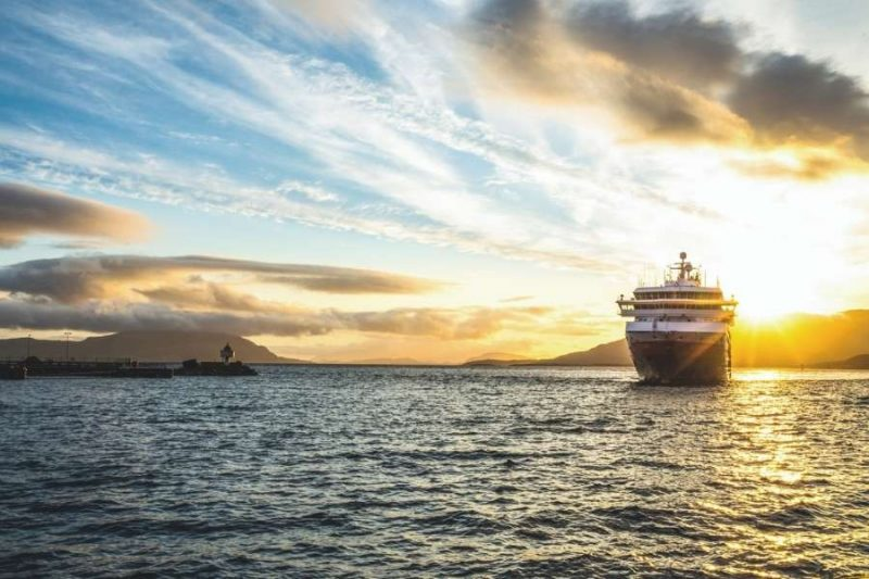 Hurtigrutenschip bij ondergaande zon