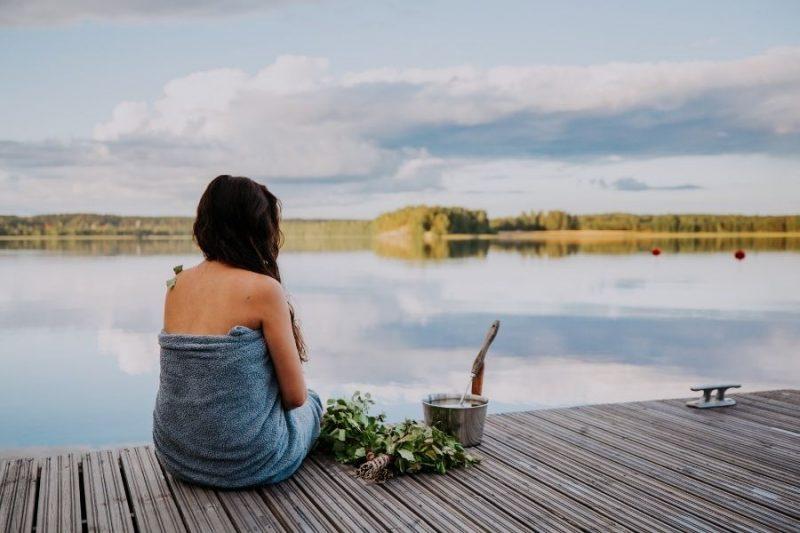 Vrouw geniet na van de sauna aan een meer in Finland