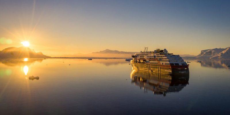 Een Hurtigrutenschip bij de ondergaande zon op exploratiereis met Nordic